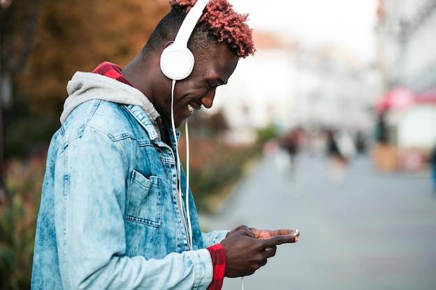Vista lateral chico con auriculares y teléfono inteligente