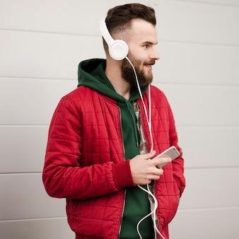 Vista lateral chico con barba y teléfono inteligente