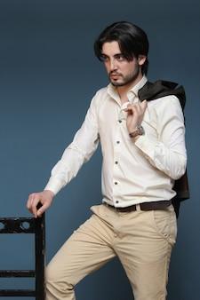 Vista lateral del chico guapo de moda agradable con chaqueta de traje sobre su hombro y posando y apoyado en una silla
