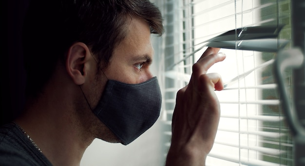 Vista lateral del chico con máscara protectora mirando por la ventana a través de las persianas, primer plano en la cabeza