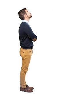 Vista lateral de chico mirando hacia arriba con los brazos cruzados