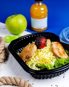 Vista lateral de chuleta de pollo con arroz y tomate en una caja de entrega