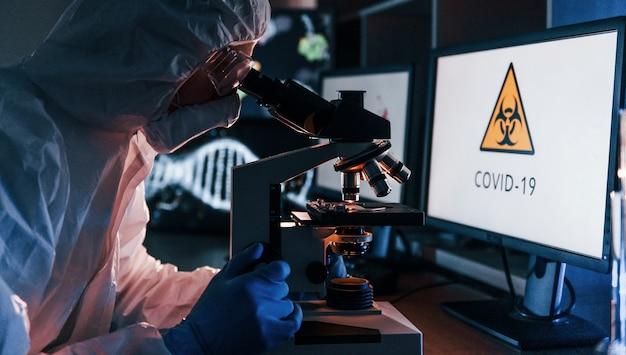 Vista lateral del científico en uniforme protector blanco que trabaja con coronavirus en laboratorio