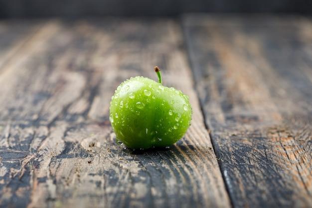 Vista lateral de ciruela verde frío en la pared de madera vieja