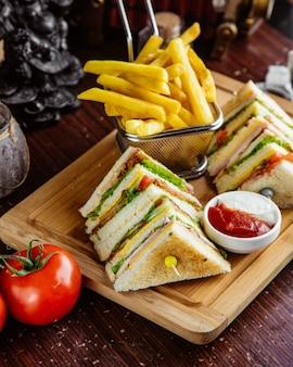 Vista lateral club sandwich con papas fritas y salsa de tomate con mayonesa