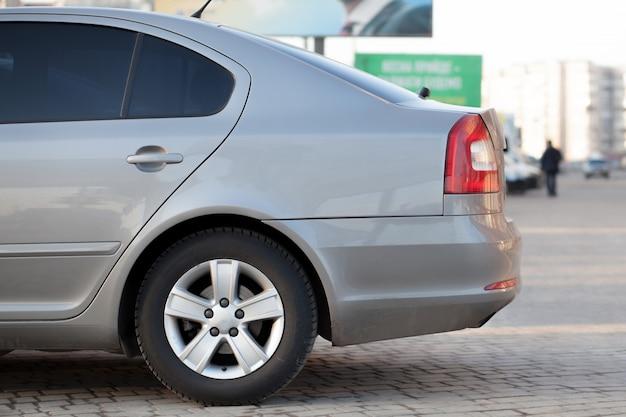 La vista lateral del coche de plata estacionó en área de estacionamiento pavimentada en fondo borroso del camino del suburbio en día soleado brillante. concepto de transporte y estacionamiento.