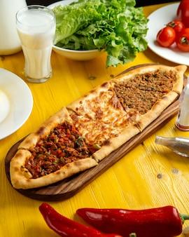 Vista lateral de la cocina turca tradicional pizza turca pita pide con un relleno diferente carne rebanadas de queso de ternera y verduras en la mesa de madera