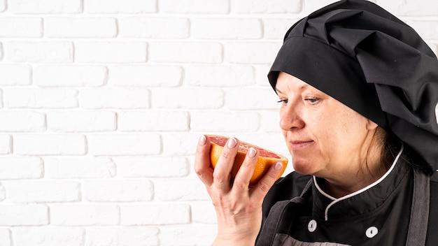 Vista lateral de la cocinera que huele a pomelo
