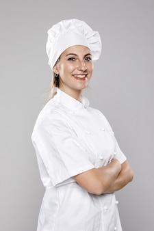 Vista lateral de la cocinera sonriente