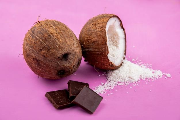 Vista lateral de cocos frescos y marrones con polvo de coco y barra de chocolate sobre superficie rosa