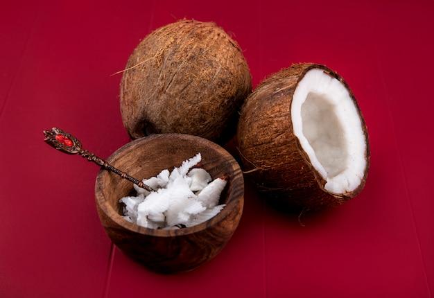 Vista lateral de cocos marrones con pulpas de coco enteras y partidas a la mitad en un recipiente de madera sobre una superficie roja.