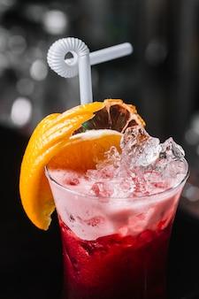 Vista lateral cóctel de frutas con una rodaja de hielo de naranja y paja en el cristal