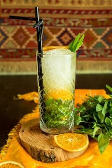 Vista lateral del cóctel mojito con hielo y naranja en un vaso