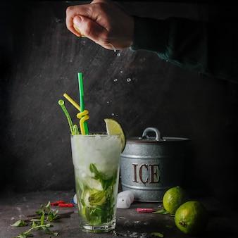 Vista lateral cóctel mojito con menta, limón, hielo, cubo de hielo