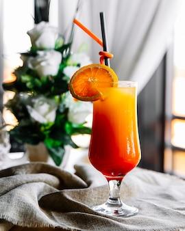 Vista lateral cóctel de naranja con rodaja de naranja y paja en el vaso