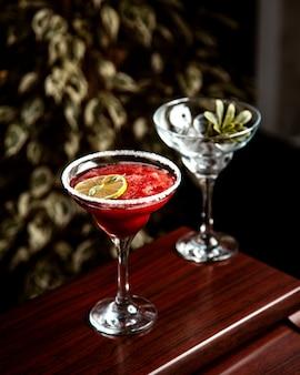 Vista lateral de un cóctel rojo con hielo picado y una rodaja de limón en vaso sobre la mesa