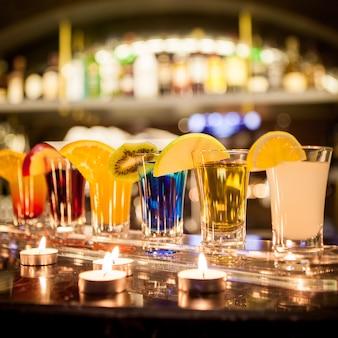 Vista lateral de cócteles con rodaja de limón y manzana y velas en la barra