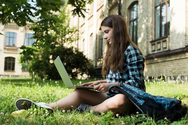 Vista lateral de la colegiala usando laptop