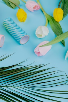 Vista lateral de coloridas flores de tulipán y rollos de cinta adhesiva sobre fondo azul.