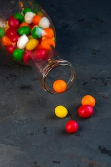 Vista lateral de coloridos dulces en una botella de vidrio sobre negro