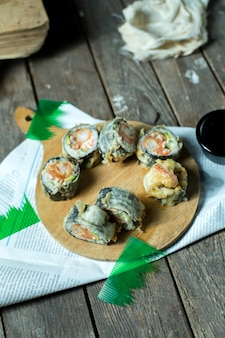 Vista lateral de la comida tradicional japonesa tempura sushi maki servido con jengibre y salsa de soja sobre tabla de madera