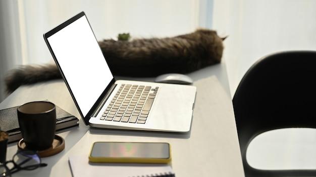 Vista lateral de la computadora portátil, teléfono inteligente, taza de café y gato en la mesa blanca.