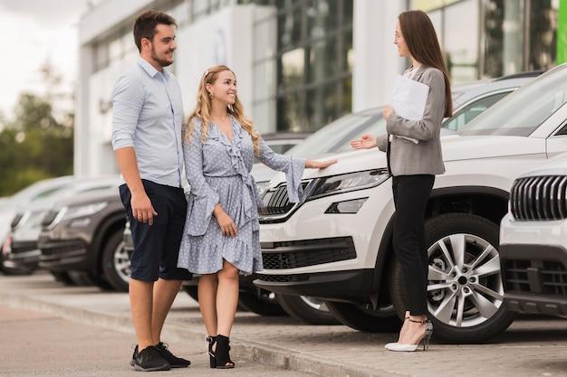 Vista lateral del concesionario de automóviles bienvenida pareja encantadora