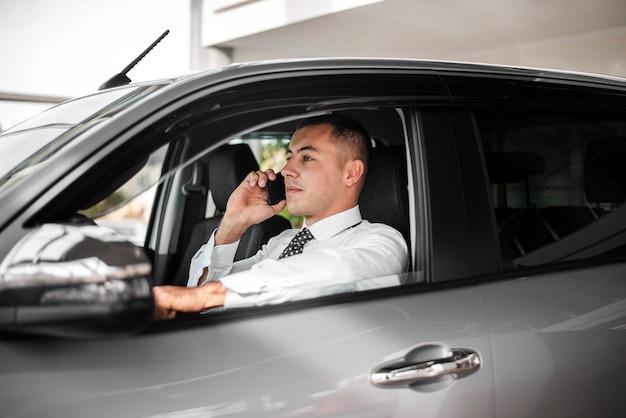 Vista lateral del concesionario de automóviles hablando por teléfono
