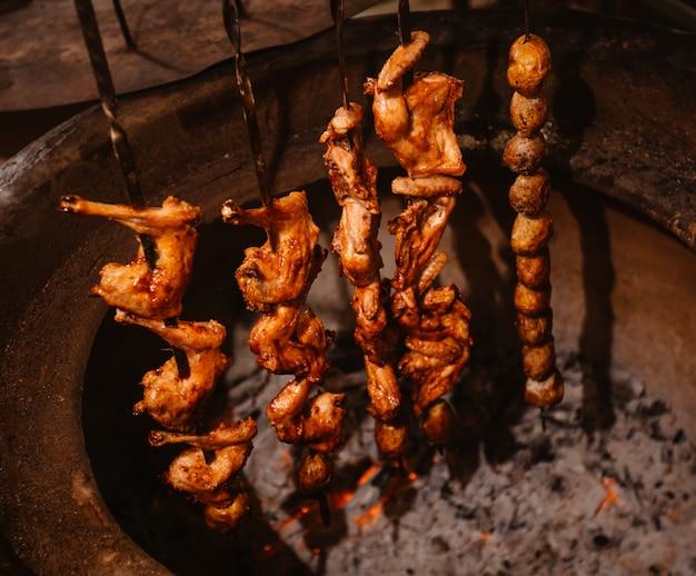 Vista lateral del conjunto de shish kebab al horno en un horno de barro