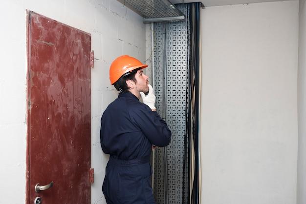 Vista lateral de contemplar al electricista de sexo masculino que mira lejos