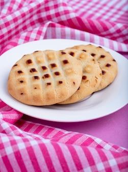 Vista lateral de las cookies en un plato blanco sobre rosa