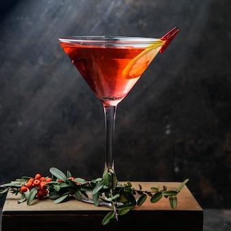 Vista lateral copa de cóctel martini rojo con limón y bayas rojas