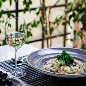 Vista lateral copa de vino con pasta en plato redondo