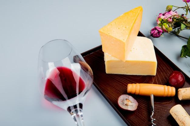 Vista lateral de una copa de vino tinto con flores y uvas parmesano y queso cheddar corchos y sacacorchos en tabla de cortar en mesa blanca