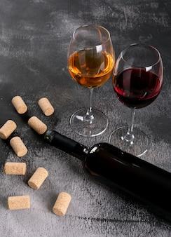 Vista lateral copas de vino con botella en piedra negra vertical