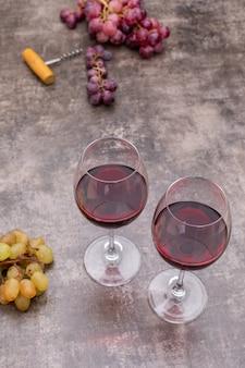 Vista lateral copas de vino rojo y uva en piedra oscura vertical