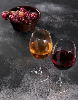 Vista lateral copas de vino con uva en piedra negra vertical