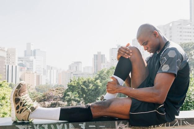 Vista lateral de un corredor de fitness masculino sentado en la azotea estirando su pierna
