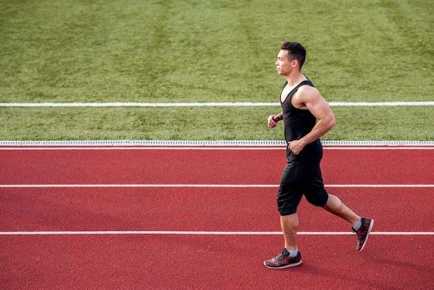 Vista lateral de un corredor masculino velocista en la pista de carreras corriendo