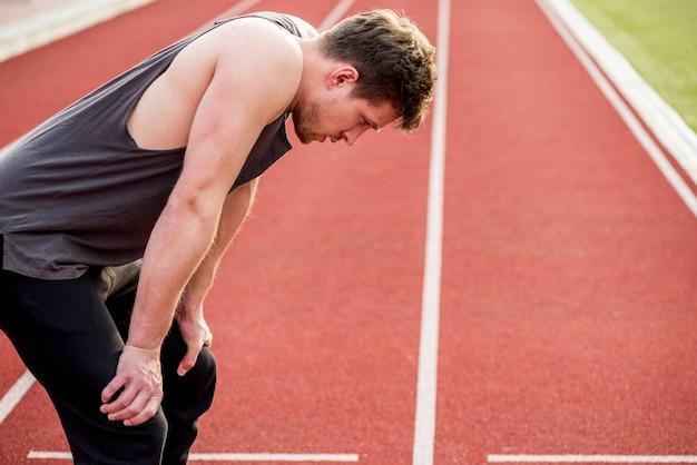 Vista lateral de un corredor masculino velocista en pista después de la carrera