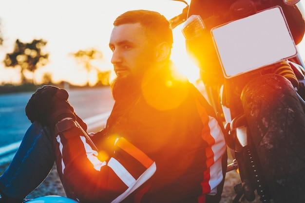 Vista lateral de la cosecha del atractivo hombre barbudo con chaqueta protectora sentado por la noche en la rueda trasera de la motocicleta en el fondo borroso retroiluminado de la carretera vacía