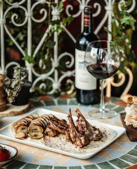 Vista lateral de costilla de cordero a la parrilla con carne de res y papas en rodajas al horno sobre la mesa servida con una botella de vino