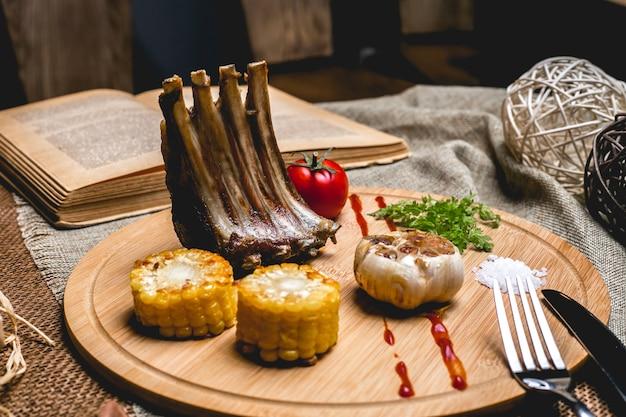 Vista lateral costillas de cordero a la parrilla con maíz, ajo, tomate y sal en un tablero