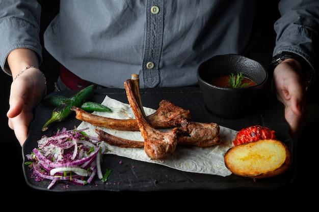 Vista lateral costillas costillas a la parrilla sobre pan de pita con papas al horno, pimientos, tomate y salsa