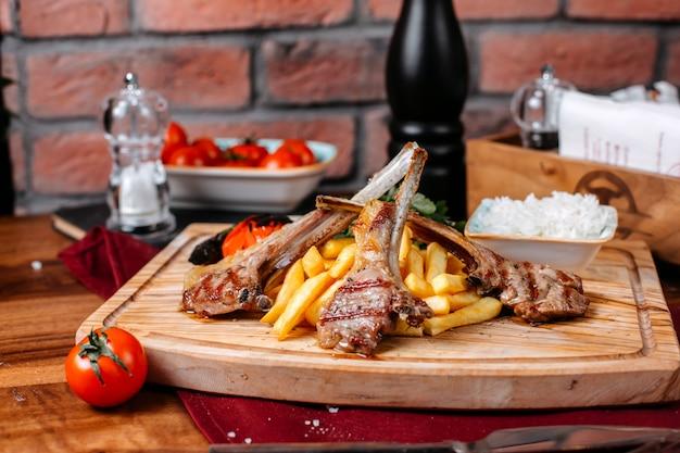 Vista lateral de costillas kebab con papas fritas arroz y verduras sobre una plancha de madera
