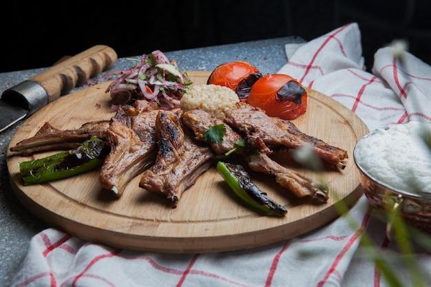 Vista lateral costillas de kebab con verduras fritas y cebolla picada y cuchillo y ayran en bandeja de comida de madera