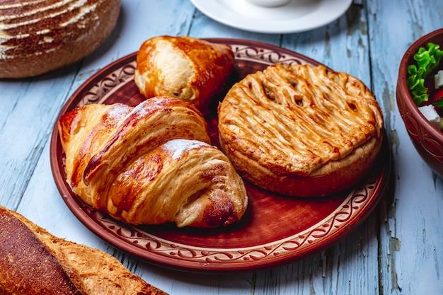 Vista lateral croissant de productos horneados con azúcar en polvo y hojaldre en un plato