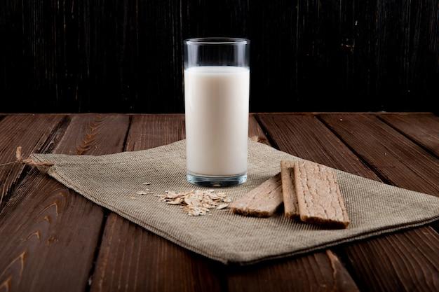 Vista lateral crujiente de pan crujiente con avena y vaso de leche en la mesa de madera