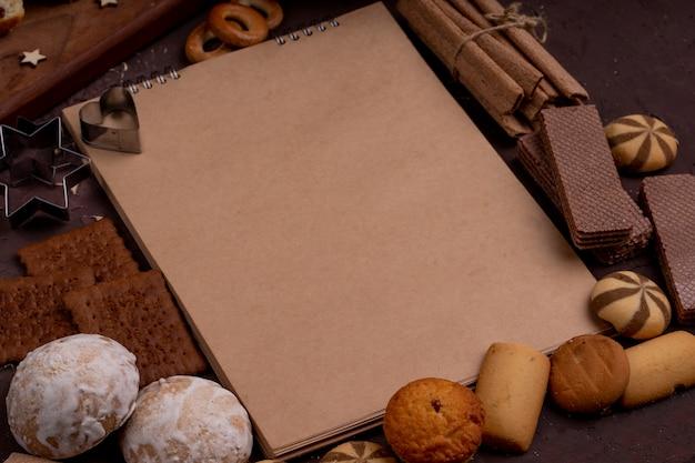 Vista lateral del cuaderno de bocetos con diferentes galletas alrededor de muffins de pan de jengibre, waffles y palitos crujientes en la oscuridad