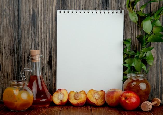 Vista lateral del cuaderno de dibujo y una botella de aceite de oliva y un frasco de vidrio con mitades de miel de nectarinas dulces frescas y un frasco de vidrio con mermelada de durazno en madera rústica